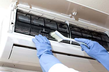 Technician professionally cleaning dust and debris from air conditioning indoor heat pump unit with brush