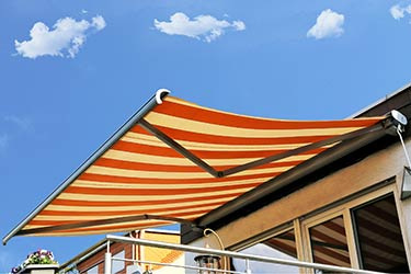Retro red and white striped retractable patio awning against beautiful blue sky