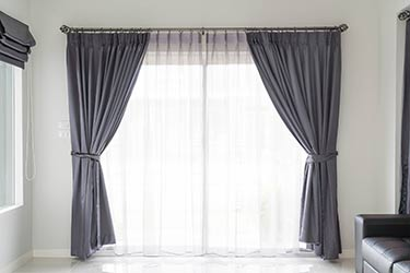 Plush satin curtains and matching shades in stylish home
