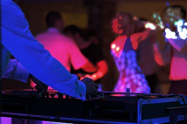 Colorful shot of DJ playing music to guests on a dancefloor