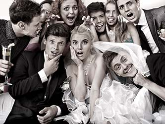 Guests posing for mobile photobooth at wedding, being silly and having fun