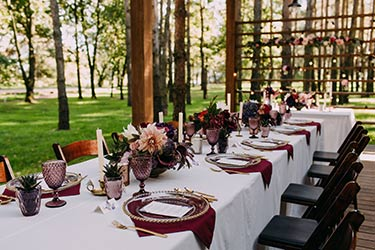 Outdoor floral banquet table in forest setting at dusk