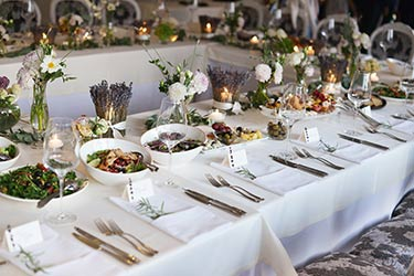 Table settings for catered dinner, framed by charming fresh floral arrangements