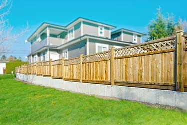 Extensive trellis top timber boundary fencing at suburban home