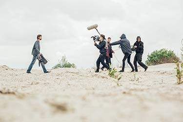Man walking across sand towards film crew with cameras and microphones working on video production