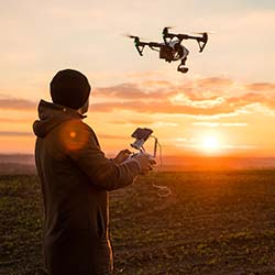 Film production team member operating drone outside with camera attached to capture video