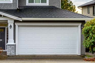 Classic new white sectional garage door on large modern house