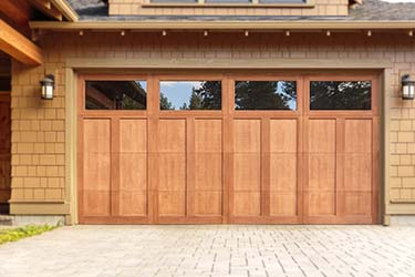 Attractive warm wood sectional garage door with built in windows