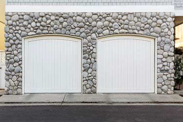 Stylish white painted curved wood garage doors fitted into interesting stone building facade
