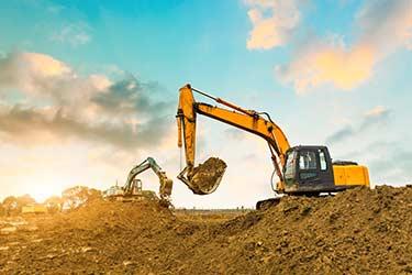 Multiple excavators work to clear earth on job site