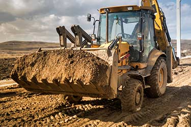 Backhoe Loader moves earth from construction site