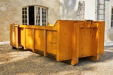 Large yellow metal dumpster on job site, ready to collect rubbish and debris during construction job