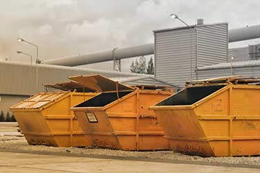 Multiple large yellow metal dumpsters for collection of construction waste