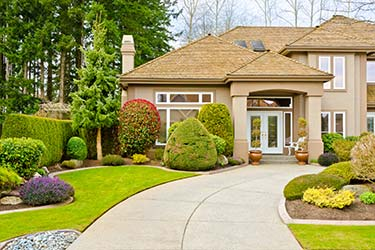 Luxurious front garden landscaping of upmarket suburban home, featuring shrubbery and topiary throughout