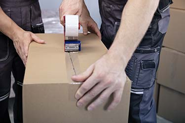 Two movers securely tape up cardboard moving box