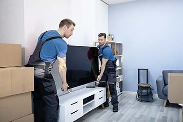 Professional movers carefully shift modern flat screen TV