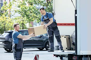 Professional moving team unloading cardboard boxes from truck
