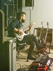 Guitarist with multiple guitars and pedal board recording tracks for album in professional recording studio