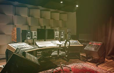 Stylish recording studio control desk with both analog and digital technology in soundproofed room