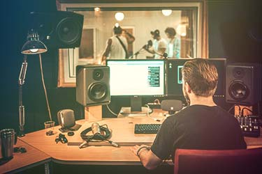 Recording studio sound engineer in control room recording band playing live music