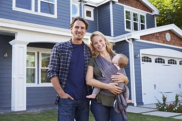 Happy young family smiling outside beautiful, freshly painted home