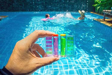 Pool cleaner holding pool water chemical test, showing results for pH levels, chlorine, and more
