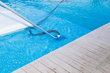 Pool vacuum as part of thorough pool maintenance, resulting in sparkling clean pool water