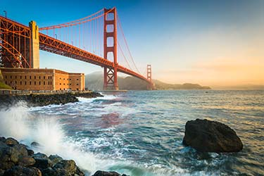 Must-see tourist hotspot, San Francisco Golden Gate Bridge, from the shore below with waves crashing at golden hour