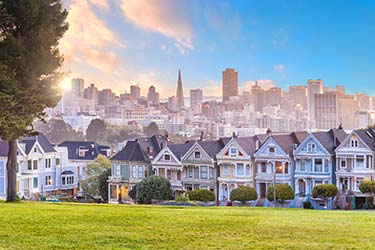 View of tourist hotspot Painted Ladies from Alamo Square Park with the San Francisco city skyline in the background