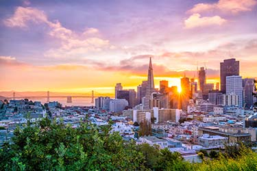 Stunning San Francisco city skyline, bathed in golden light, with the Golden Gate Bridge in the background