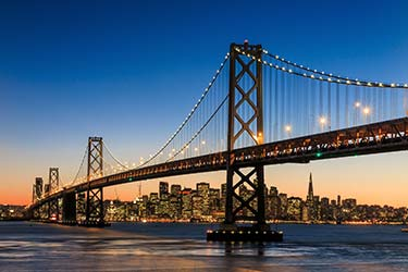 The glorious Golden Gate Bridge lit up at night with the San Francisco city skyline in the background