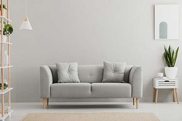 Plush sofa in light, airy lounge area, skilfully upholstered in quality grey linen material