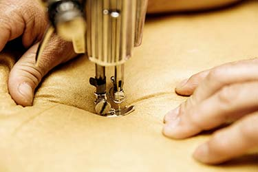 Upholsterer operates sewing machine on delicate leather material